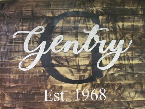 "White ""Gentry"" and ""Est. 1968"" painted onto brown wood stained board with a black ""G"" in background"