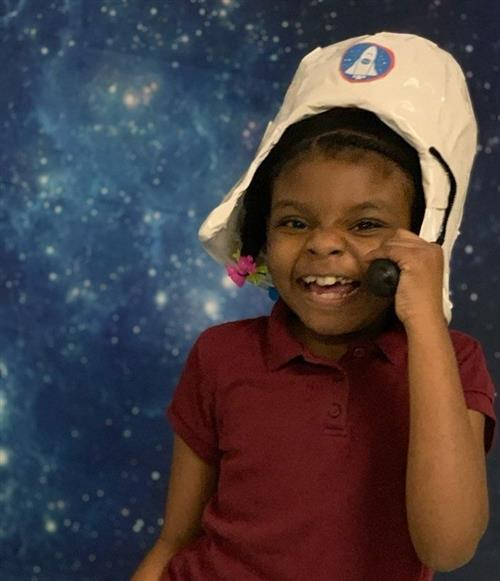 A young girl wearing an astronaut hat and smiling