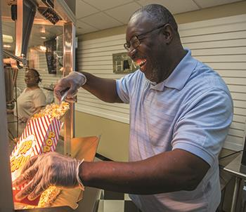A student in EHG's Business Enterprise Program fills a bag of popcorn for a customer