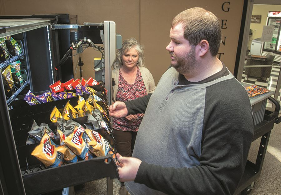 A student in the EHG's Business Enterprise Program learns to stock a vending machine
