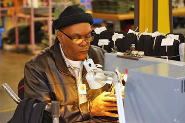 David Marshall sits at his sewing machine on the AIB production floor as he manufacturers a nectie.
