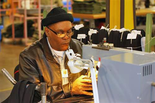 David Marshall sits at his sewing machine on the AIB production floor as he manufacturers a necktie.