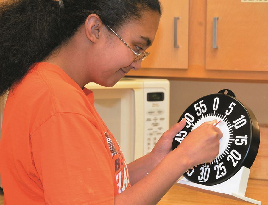A DeafBlind client at EHG learns to use a timer with oversized numbers