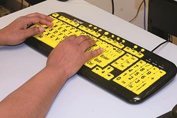 A closeup of two hands typing on a keyboard with large-sized keys for DeafBlind clients at EGH