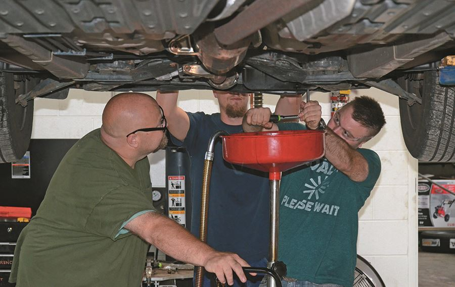 EHG clients receive instruction on how to change a car's oil