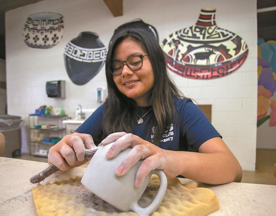 An EHG client does ceramics as part of the extended daycare and recreation program