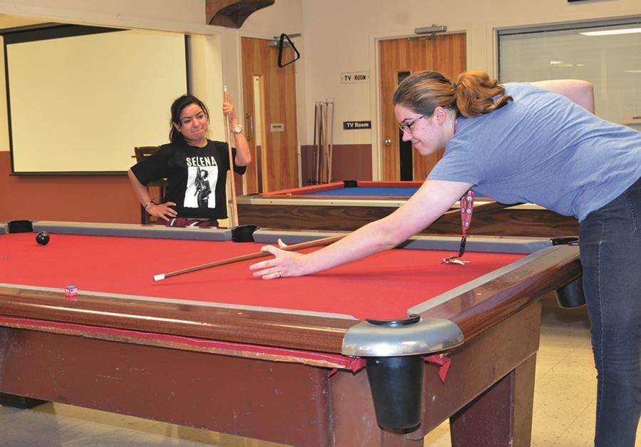 Two EHG clients shoot pool as part of the extended daycare and recreation program