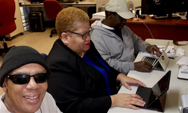Two adult clients who are blind working with the teacher on mobile devices
