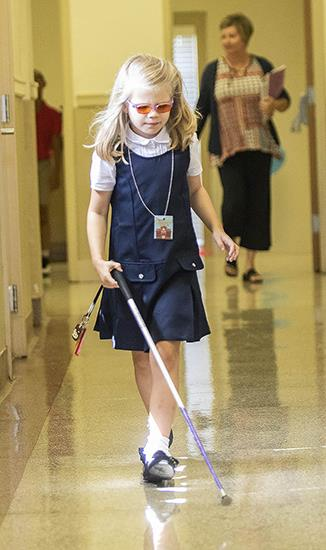 Photo of young girl walking the hall at ASB using her cane.