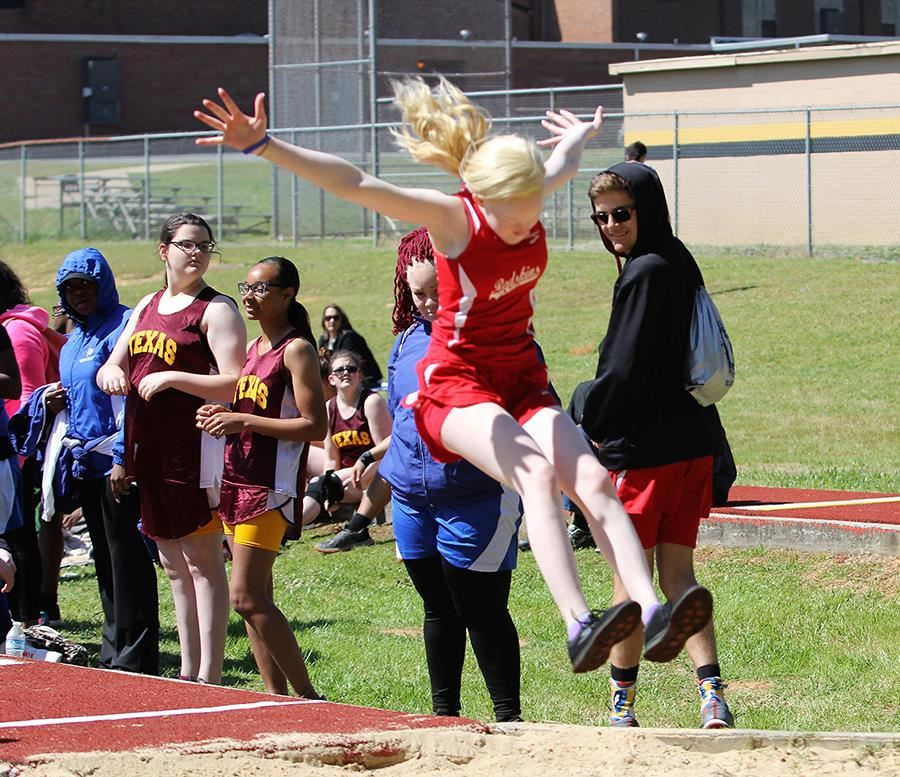A member of the ASB girls' track team competes in the long jump event