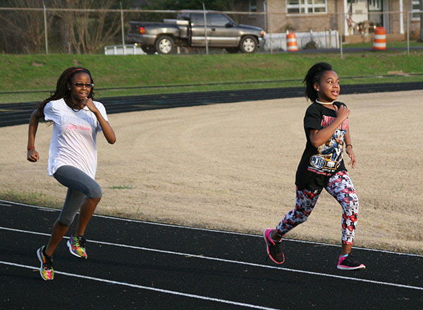 Two ASB track team members running during practice
