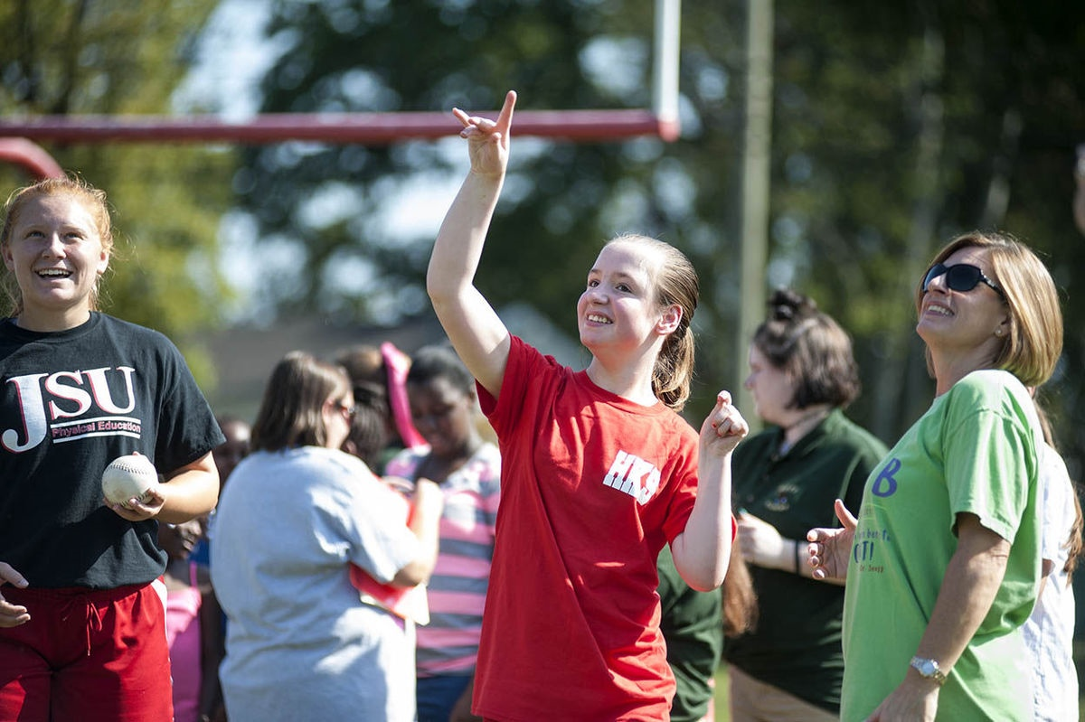 A female student participates in the softball throw as her teacher looks on.