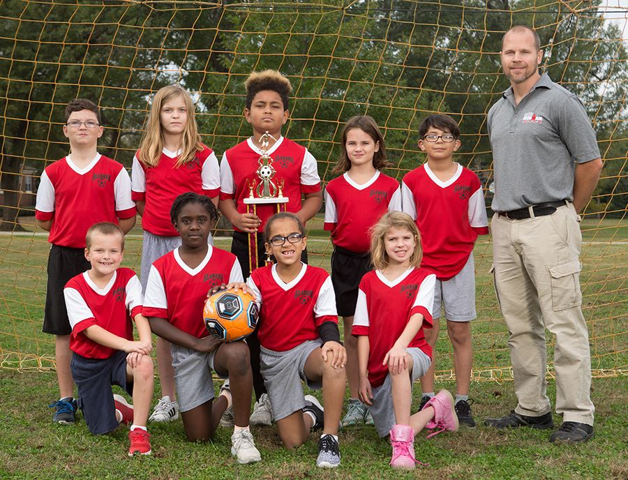 Members of the 2018-19 ASD Rec League Minor soccer team pose for a team photo in front of a soccer net.