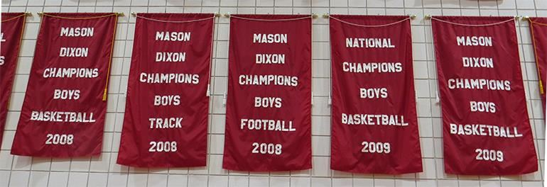 Photo of many ASD athletic championship banners on display in the gym