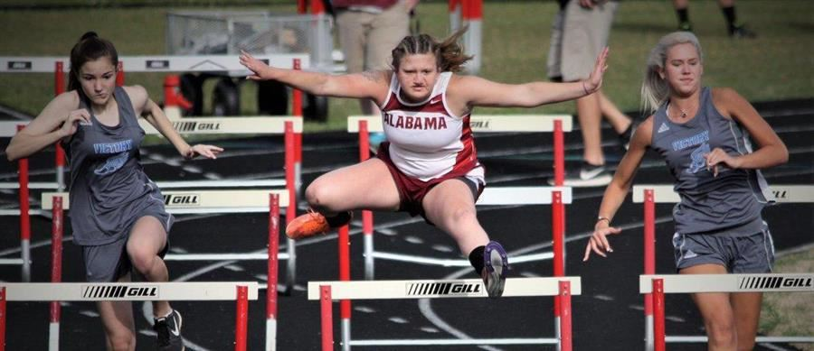 Addison leaping over a hurdle at a track meet.