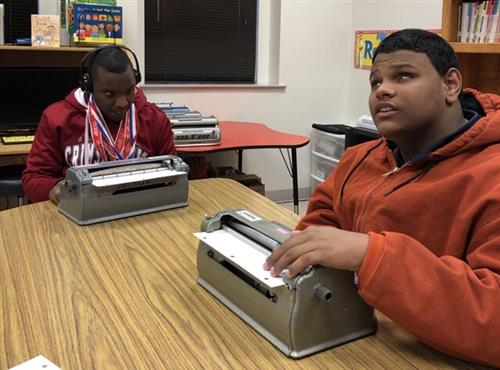 two boys on their braille writers