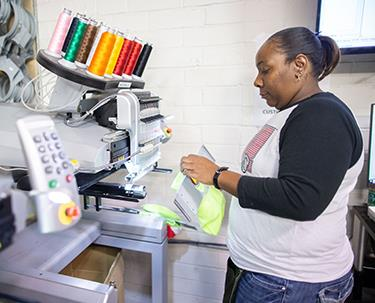 An AIB employee programs an embroidery machine