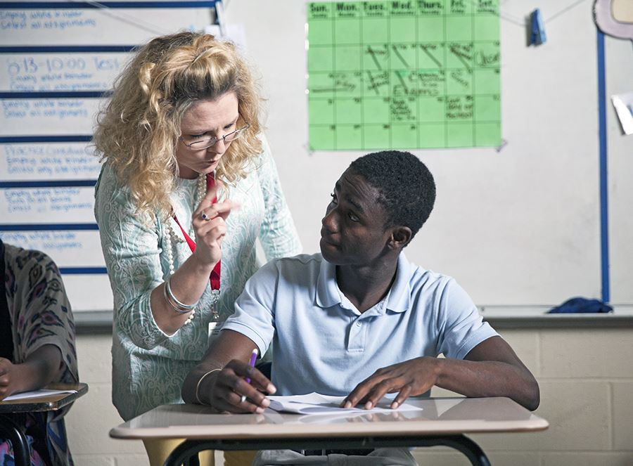 A teacher  helps an ASD student during class
