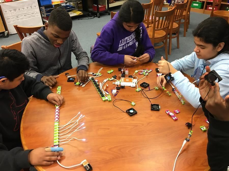 Group of students at a table working on electronics called Little Bits