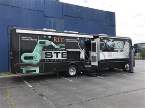 Picture of an RV with design of robot and drone.  STEM, RIT and AIDB logos are on it
