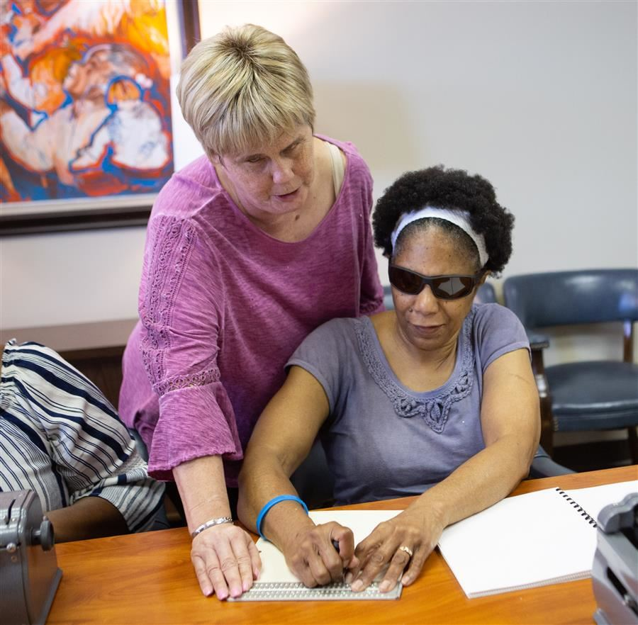 Two people who are blind reading Braille.
