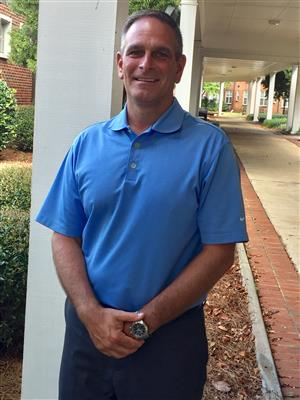 Man wearing blue shirt standing on a sidewalk in front of an Alabama School for the Blind building