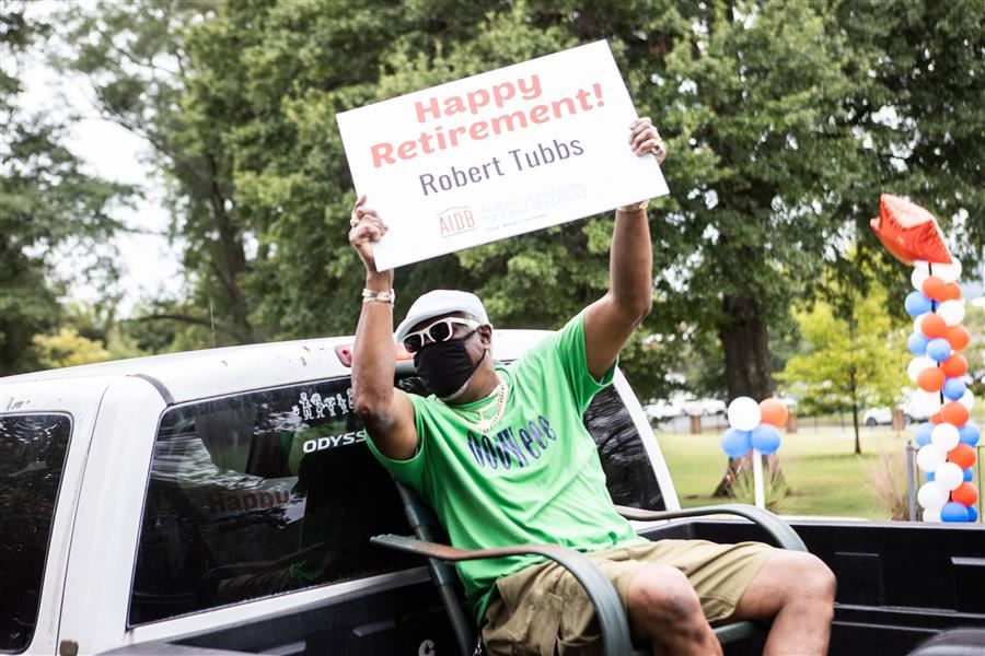 Retiree Mr. Tubbs holding a sign that says Happy Retirement!