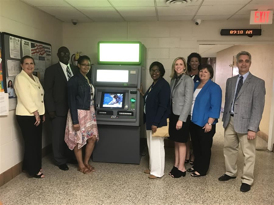Representatives of Regions Bank and AIDB stand with the newly installed ATM at E. H. Gentry