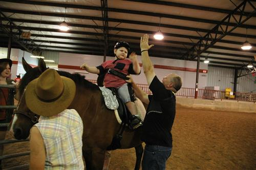 Volunteer giving a high five to a student on horseback
