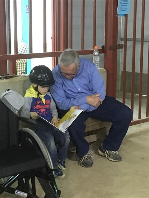 male volunteer sits and reads book with young student