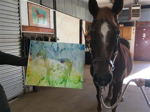 brown horse standing next to a blue, green, and yellow painted canvas