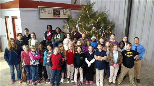 large group of 32 students in front of Christmas tree