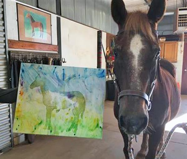 MGHSE horse Image standing beside a watercolor painting he painted with his tongue.