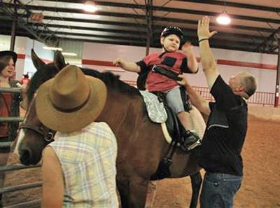 A volunteer gives a student on horseback at the MGHSE arena a high five.