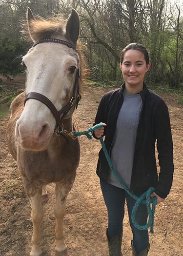 MGHSE student worker Anna stands beside a horse