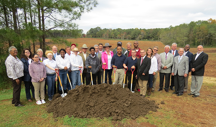 The JTA Ground Breaking. There are students and staff holding shovels in the ground.
