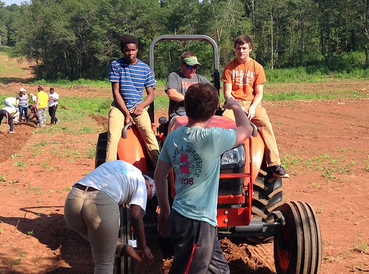 Several students and teacher are on a tractor plowing a feild.
