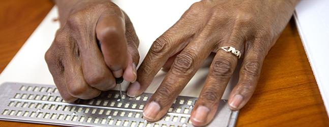 Closeup photo of the hands of a client writing in braille