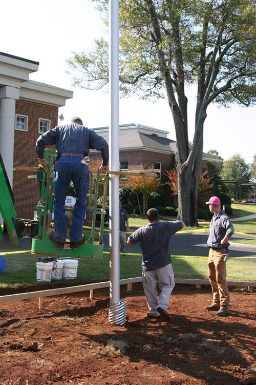 Maintenance men set new flag pole